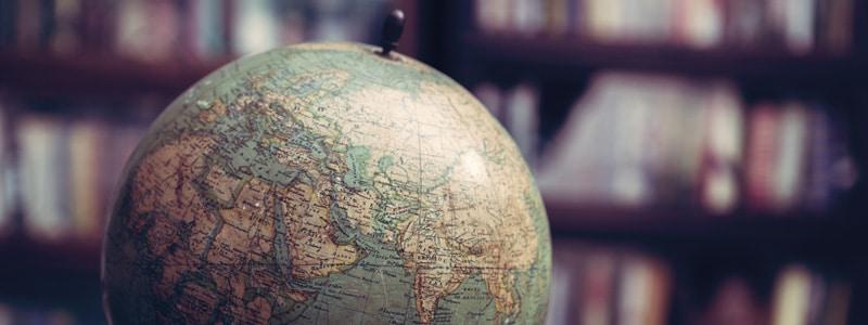 Globus, welcher vor einem Bücherregal steht.