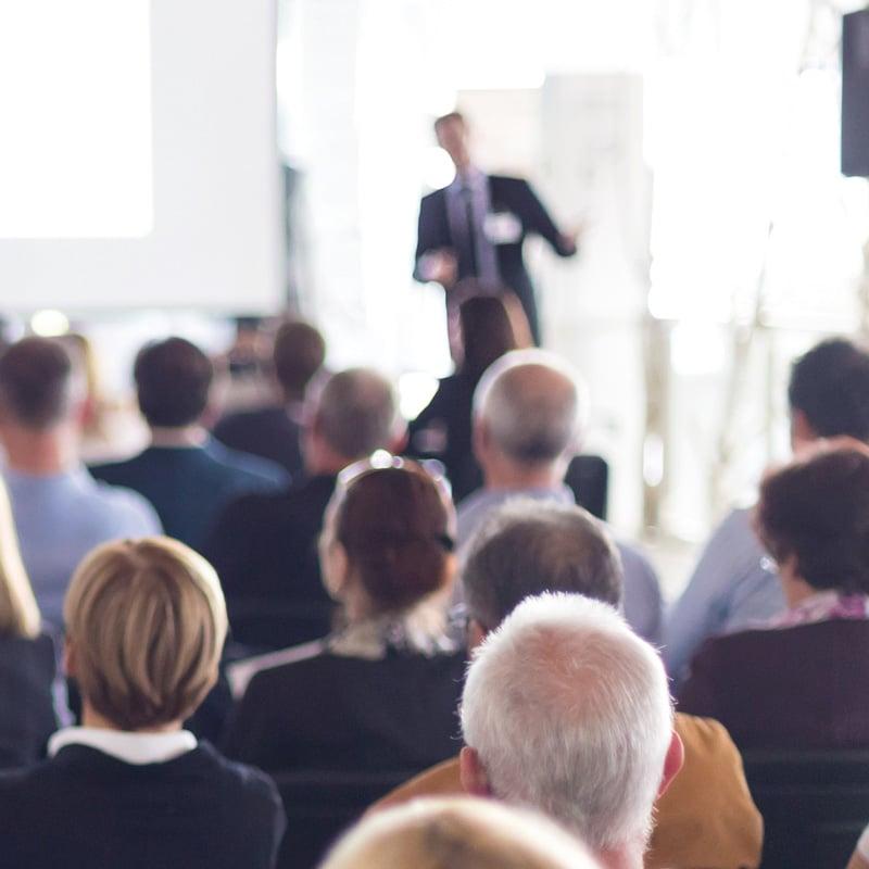 Redner, der einen Vortrag vor Publikum hält.