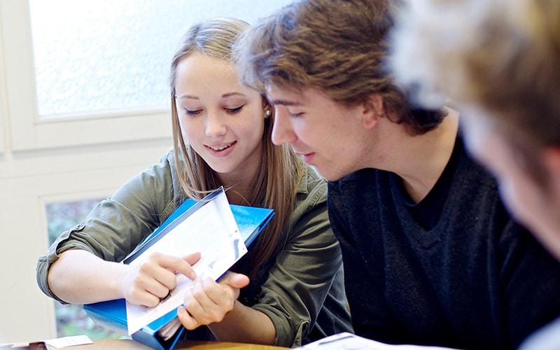 Eine Studentin und zwei Studenten befassen sich mit Arbeitsmaterialien